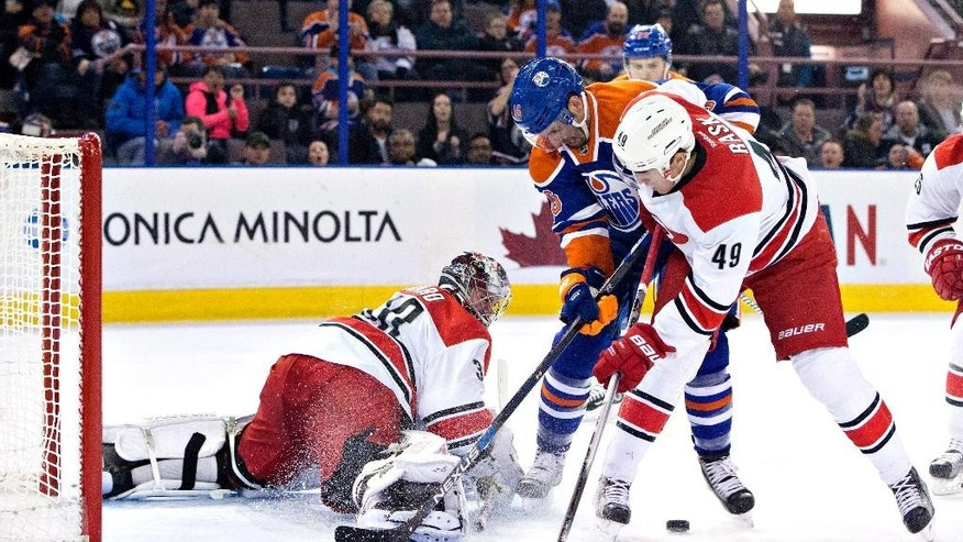 Carolina Hurricanes' goalie Cam Ward (30) makes the save as Victor Rask (49) and Edmonton Oilers' Teddy Purcell (16) battle for the rebound during second period NHL action in Edmonton, Alberta, Monday, Jan. 4, 2016. (Jason Franson/The Canadian Press via AP)