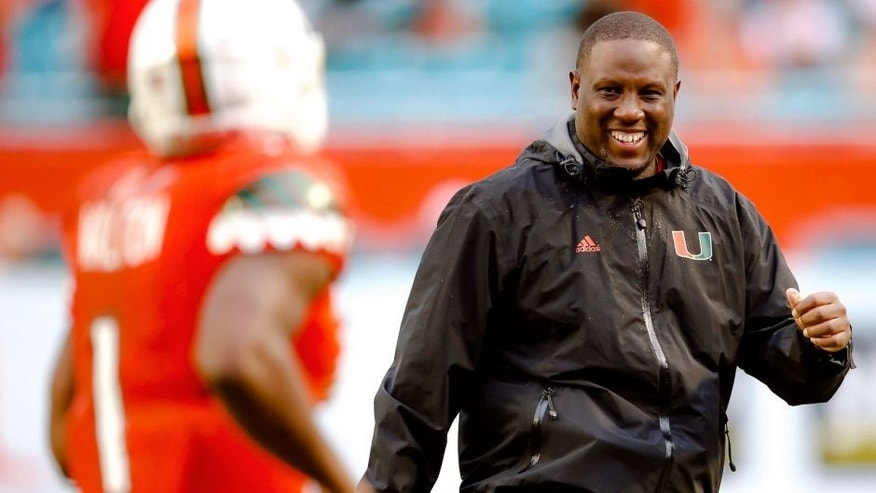 Nov 21, 2015; Miami Gardens, FL, USA; Miami Hurricanes interim head coach Larry Scott (right) greets Hurricanes running back Mark Walton (left) after Walton scored a touchdown against the Georgia Tech Yellow Jackets during the second half at Sun Life Stadium. Mandatory Credit: Steve Mitchell-USA TODAY Sports