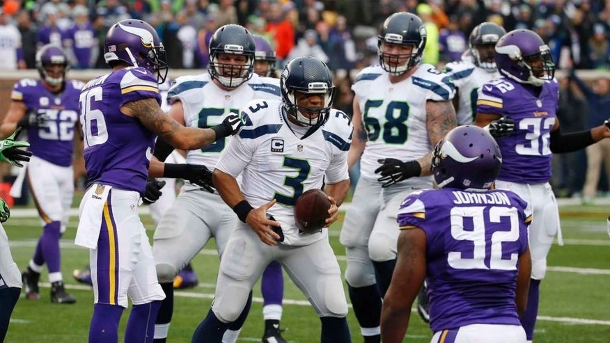 Seattle Seahawks quarterback Russell Wilson celebrates his 8-yard touchdown run against the Minnesota Vikings in the first half of an NFL football game Sunday, Dec. 6, 2015, in Minneapolis.