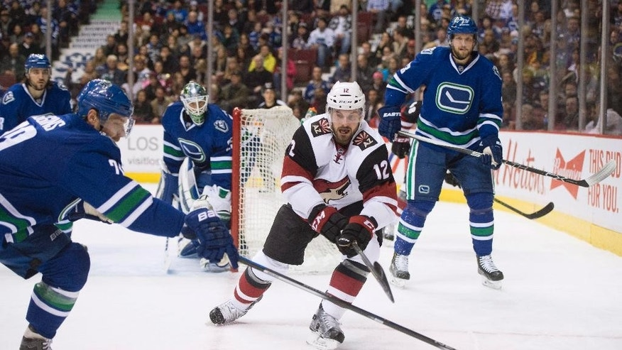 Arizona Coyotes center Brad Richardson (12) fights for control of the puck with Vancouver Canucks left wing Chris Higgins (20) and Vancouver Canucks defenseman Alexander Edler (23) during first period NHL action Vancouver,  British Columbia, Monday, Jan. 4, 2016. (Jonathan Hayward/The Canadian Press via AP)