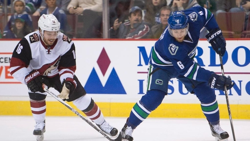 Vancouver Canucks defenseman Yannick Weber (6) fights for control of the puck with Arizona Coyotes center Max Domi (16) during first period NHL action Vancouver,  British Columbia, Monday, Jan. 4, 2016. (Jonathan Hayward/The Canadian Press via AP)