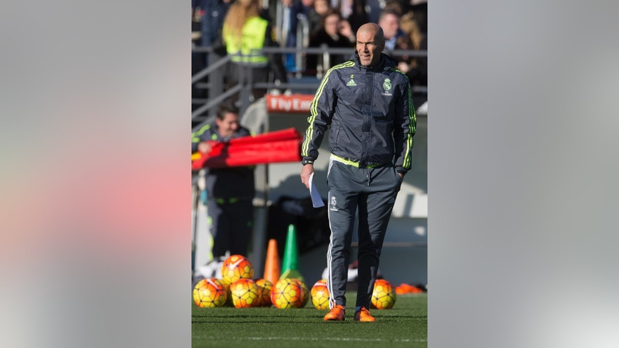 Real Madrid's newly appointed coach Zinedine Zidane watches his players during his first training session in Madrid, Spain, Tuesday Jan. 5, 2016. Real Madrid fired coach Rafael Benitez Monday after seven months and replaced him with former player Zinedine Zidane a day after Madrid's 2-2 draw at Valencia deepened a crisis that started with an embarrassing 4-0 home loss to rival Barcelona in November. (AP Photo/Paul White)
