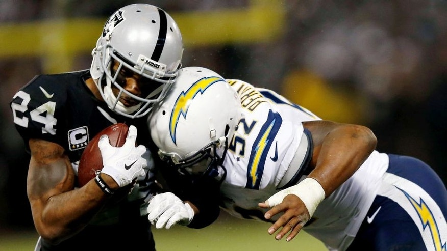 OAKLAND, CA - DECEMBER 24: Safety Charles Woodson #24 of the Oakland Raiders is tackled by linebacker Denzel Perryman #52 of the San Diego Chargers in overtime at O.co Coliseum on December 24, 2015 in Oakland, California. (Photo by Lachlan Cunningham/Getty Images)