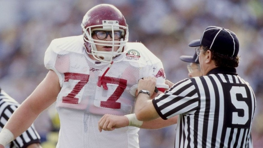 1 Jan 1999: Brandon Burlsworth #77 of the Arkansas Razorbacks is helped by an official during the Citrus Bowl against the Michigan Wolverines at the Florida Citrus Bowl in Orlando, Florida. Michigan defeated Arkansas 45-31. Mandatory Credit: Andy Lyons /Allsport