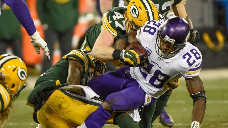 <p>Jan 3, 2016; Green Bay, WI, USA; Minnesota Vikings running back Adrian Peterson (28) tries to break a tackle by Green Bay Packers linebacker Jake Ryan (47) in the fourth quarter at Lambeau Field. Mandatory Credit: Benny Sieu-USA TODAY Sports</p>
