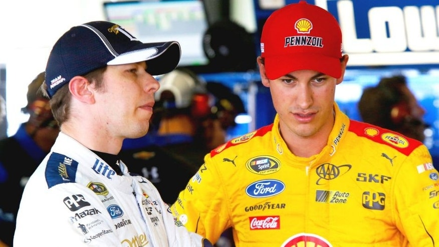 """LONG POND, PA - JUNE 05: Brad Keselowski, driver of the #2 Miller Lite Ford, left, and Joey Logano, driver of the #22 Shell Pennzoil Ford, talk in the garage area during practice for the NASCAR Sprint Cup Series Axalta """"We Paint Winners"""" 400 at Pocono Raceway on June 5, 2015 in Long Pond, Pennsylvania. (Photo by Jerry Markland/Getty Images)"""