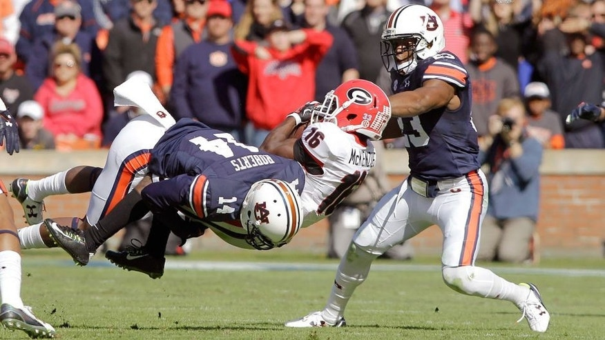Nov 14, 2015; Auburn, AL, USA; Georgia Bulldogs receiver Isaiah McKenzie (16) is tackled by Auburn Tigers defensive backs Stephen Roberts (14) and Johnathan Ford (23) during the second quarter at Jordan Hare Stadium. Mandatory Credit: John Reed-USA TODAY Sports