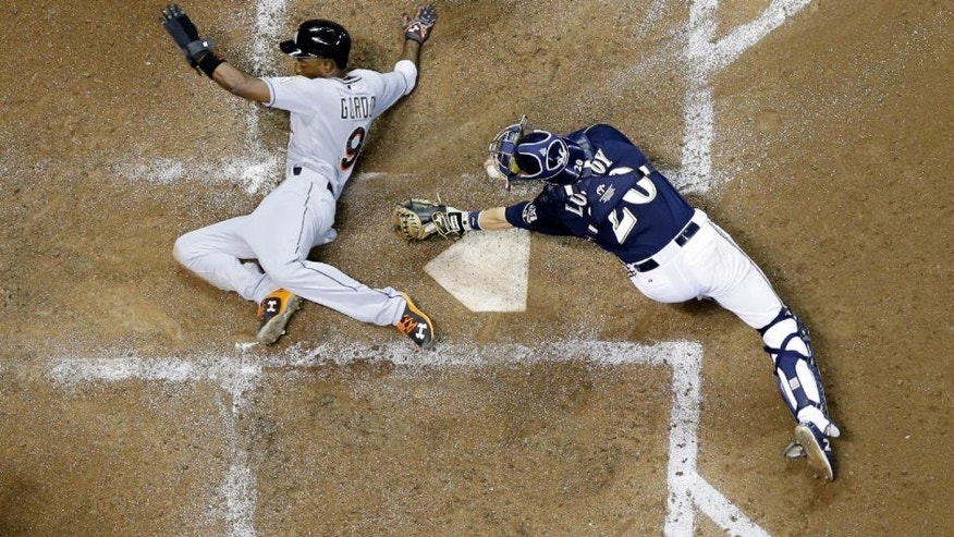 Miami Marlins' Dee Gordon slides safely past Milwaukee Brewers catcher Jonathan Lucroy during the fifth inning of a baseball game Monday, Aug. 17, 2015, in Milwaukee. Gordon scored from third on a sacrifice fly by Martin Prado. (AP Photo/Morry Gash)