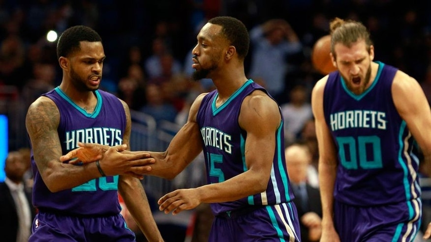Jan 22, 2016; Orlando, FL, USA; Charlotte Hornets guard Kemba Walker (15) is congratulated by guard Troy Daniels (30) and forward Spencer Hawes (00) during the second half against the Orlando Magic at Amway Center. Charlotte Hornets defeated the Orlando Magic 120-116 in overtime. Mandatory Credit: Kim Klement-USA TODAY Sports