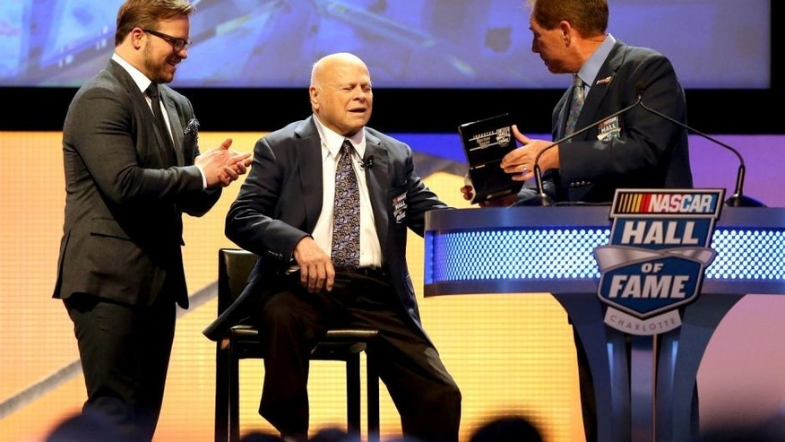 CHARLOTTE, NC - JANUARY 23: (L-R) Marcus Smith watches as his father, Bruton Smith, is inducted into the NASCAR Hall of Fame by Darrell Waltrip during the NASCAR Hall of Fame Induction Ceremony on January 23, 2016 in Charlotte, North Carolina. (Photo by Streeter Lecka/NASCAR via Getty Images)