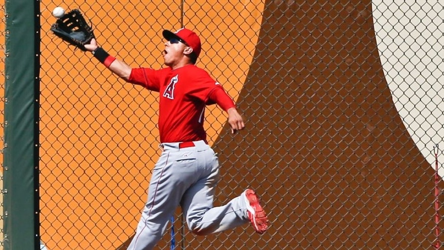 Los Angeles Angels left fielder Efren Navarro misplays the ball hit by Kansas City Royals' Alcides Escobar in the third inning of a spring training baseball game Saturday, March 14, 2015, in Surprise, Ariz. (AP Photo/Lenny Ignelzi)