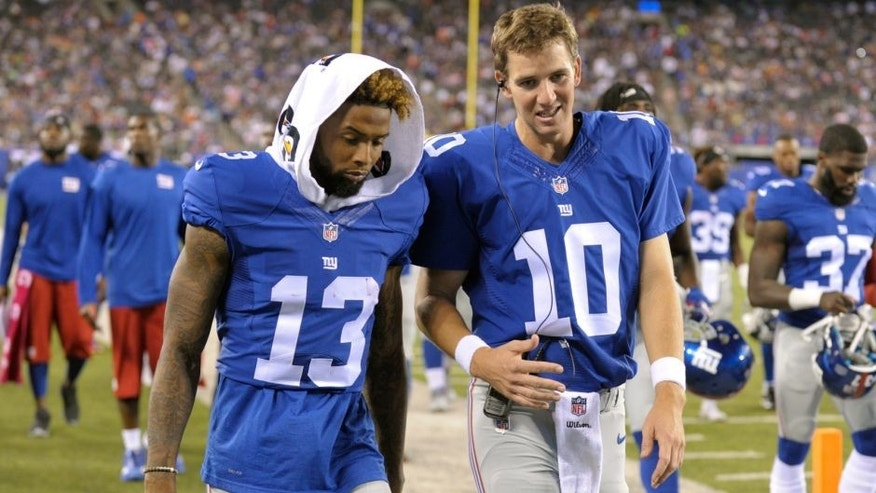 New York Giants quarterback Eli Manning (10) and Odell Beckham (13) talk while walking off the field after the first half of a preseason NFL football game against the Jacksonville Jaguars, Saturday, Aug. 22, 2015, in East Rutherford, N.J. (AP Photo/Bill Kostroun)