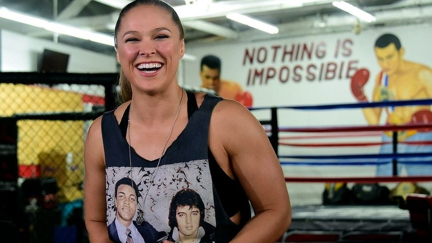 Mixed Martial Arts (MMA) fighter Ronda Rousey, wearing a shirt with portraits of former heavyweight boxing champion Muhammad Ali (L) and the late US singer Elvis Presley (R), responds to questions during media day in Glendale, California on October 27, 2015 ahead of her November 14 fight in Melbourne, Australia against Holly Holm. AFP PHOTO / FREDERIC J. BROWN (Photo credit should read FREDERIC J. BROWN/AFP/Getty Images)