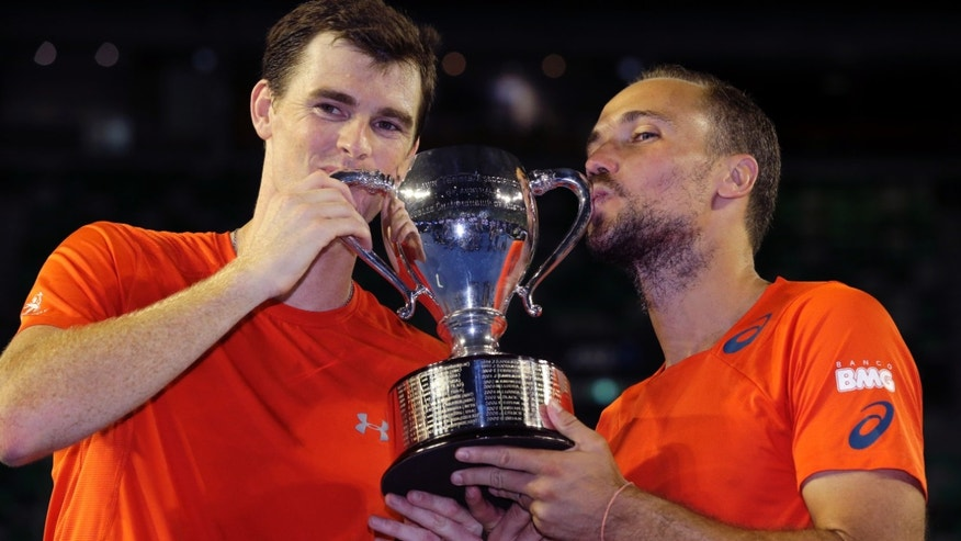 Jamie Murray, left, of Britain and Bruno Soares of Brazil hold their trophy after defeating Daniel Nestor of Canada and Radek Stepanek of the Czech Republic in the men's doubles final at the Australian Open tennis championships in Melbourne, Australia, early Sunday, Jan. 31, 2016.(AP Photo/Aaron Favila)
