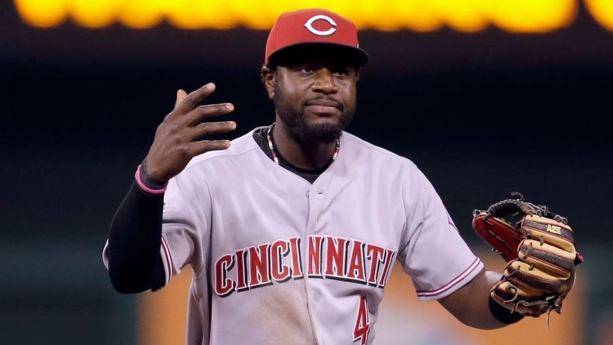 Cincinnati Reds second baseman Brandon Phillips throws up his hands after misplaying a ball hit by St. Louis Cardinals' Matt Adams during the eighth inning of a baseball game Friday, April 17, 2015, in St. Louis. The Cardinals' Matt Carpenter score and Phillips was charged with an error on the play. (AP Photo/Jeff Roberson)
