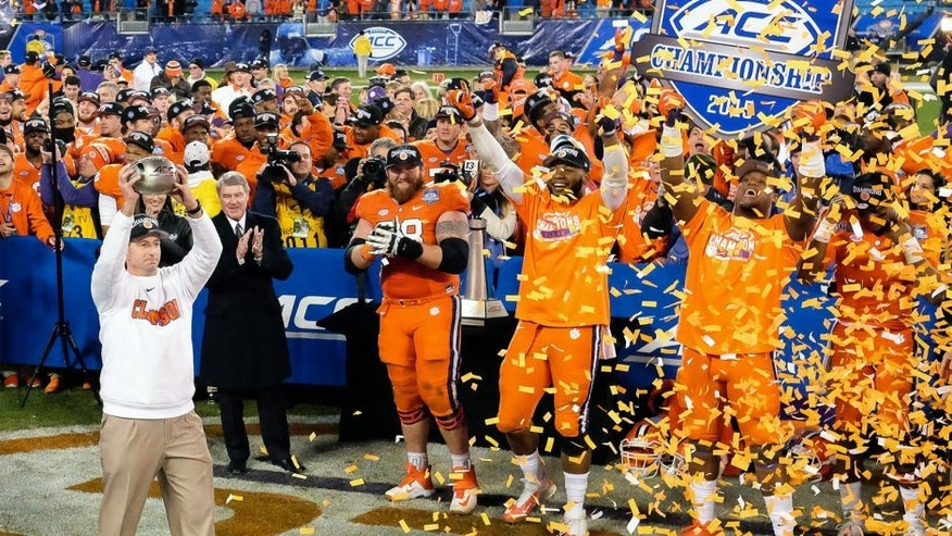 Dec 5, 2015; Charlotte, NC, USA; Clemson Tigers head coach Dabo Swinney (L) holds up the trophy for fans after winning the ACC football championship game at Bank of America Stadium. The Tigers won 45-37. Mandatory Credit: Jim Dedmon-USA TODAY Sports