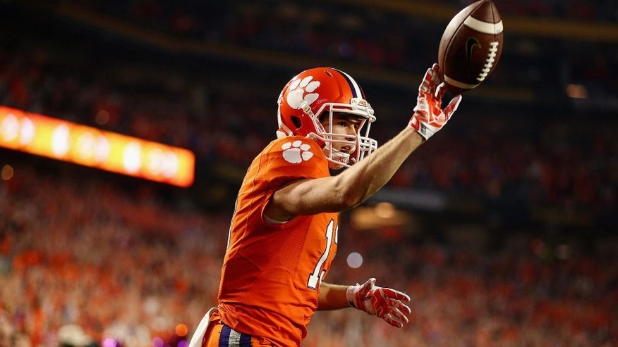 <p>GLENDALE, AZ - JANUARY 11: Hunter Renfrow #13 of the Clemson Tigers celebrates after scoring a 31 yard touchdown from Deshaun Watson #4 in the first quarter against the Alabama Crimson Tide during the 2016 College Football Playoff National Championship Game at University of Phoenix Stadium on January 11, 2016 in Glendale, Arizona. (Photo by Ronald Martinez/Getty Images)</p>