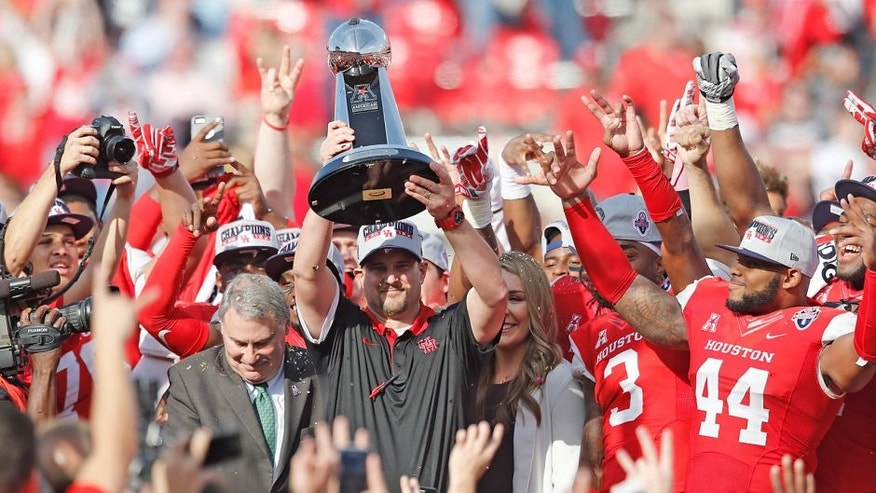 Dec 5, 2015; Houston, TX, USA; Houston Cougars head coach Tom Herman hold up the 2015 Mid-American Conference trophy after defeating the Temple Owls in the in the Mid-American Conference football championship game at TDECU Stadium. Houston won 24 to 13. Mandatory Credit: Thomas B. Shea-USA TODAY Sports