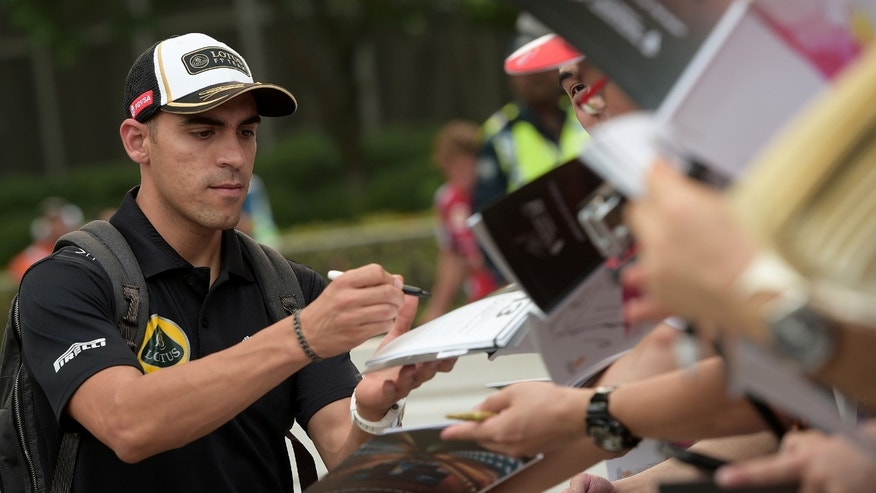 FILE - In this Sept. 18, 2015 file photo, Lotus driver Pastor Maldonado of Venezuela signs autographs for fans on his arrival at the Marina Bay City Circuit ahead of the first practice session for the Singapore Formula One Grand Prix. Maldonado announced Monday, Feb. 1, 2016, that he won't be driving in the Formula One world championships this season. (AP Photo/Joseph Nair, File)