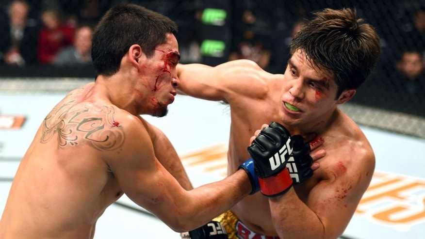 PHOENIX, AZ - DECEMBER 13: (R-L) Henry Cejudo punches Dustin Kimura in their bantamweight fight during the UFC Fight Night event at the U.S. Airways Center on December 13, 2014 in Phoenix, Arizona. (Photo by Josh Hedges/Zuffa LLC/Zuffa LLC via Getty Images)