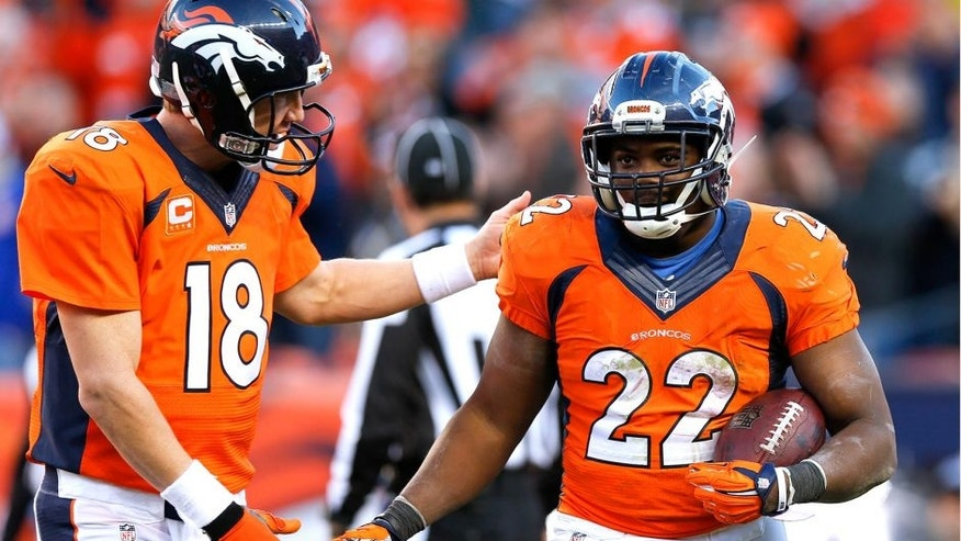 Denver Broncos running back C.J. Anderson, right, celebrates his touchdown with quarterback Peyton Manning during the second half in an NFL football game Sunday, Dec. 7, 2014, in Denver. (AP Photo/David Zalubowski)