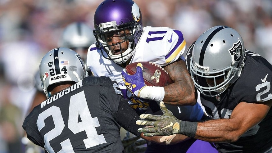 OAKLAND, CA - NOVEMBER 15: Wide receiver Mike Wallace #11 of the Minnesota Vikings is stopped by free safety Charles Woodson #24 of the Oakland Raiders and strong safety Nate Allen #20 of the Oakland Raiders in the first quarter at O.co Coliseum on November 15, 2015 in Oakland, California. (Photo by Thearon W. Henderson/Getty Images)