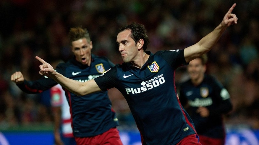 Atletico Madrid's Uruguayan defender Diego Godin (R) celebrates a goal during the Spanish league football match Granada FC VS Club Atletico de Madrid at Nuevo Los Carmenes stadium in Granada on December 5, 2015. AFP PHOTO / JORGE GUERRERO / AFP / Jorge Guerrero (Photo credit should read JORGE GUERRERO/AFP/Getty Images)