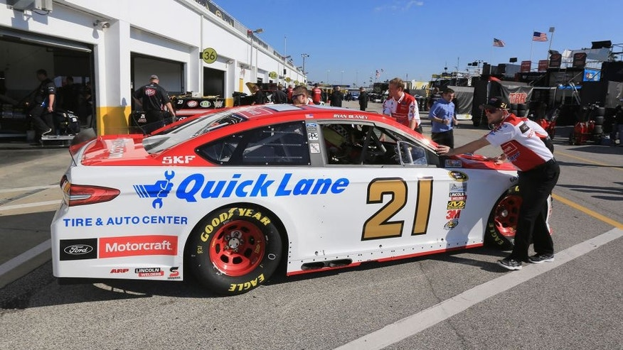 DAYTONA BEACH, FL - FEBRUARY 13: The car of Ryan Blaney (not pictured), driver of the #21 Motorcraft/Quick Lane Tire & Auto Center Ford, is pushed by crew members through the garage area during practice for the NASCAR Sprint Cup Series Daytona 500 at Daytona International Speedway on February 13, 2016 in Daytona Beach, Florida. (Photo by Jerry Markland/Getty Images)