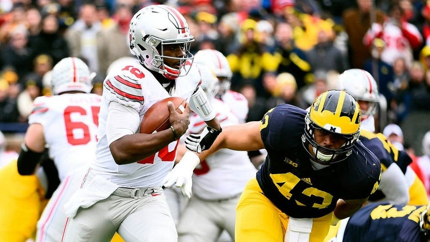 Nov 28, 2015; Ann Arbor, MI, USA; Ohio State Buckeyes quarterback J.T. Barrett (16) runs the ball Michigan Wolverines defensive end Chris Wormley (43) over to defend in the first quarter at Michigan Stadium. Mandatory Credit: Tim Fuller-USA TODAY Sports