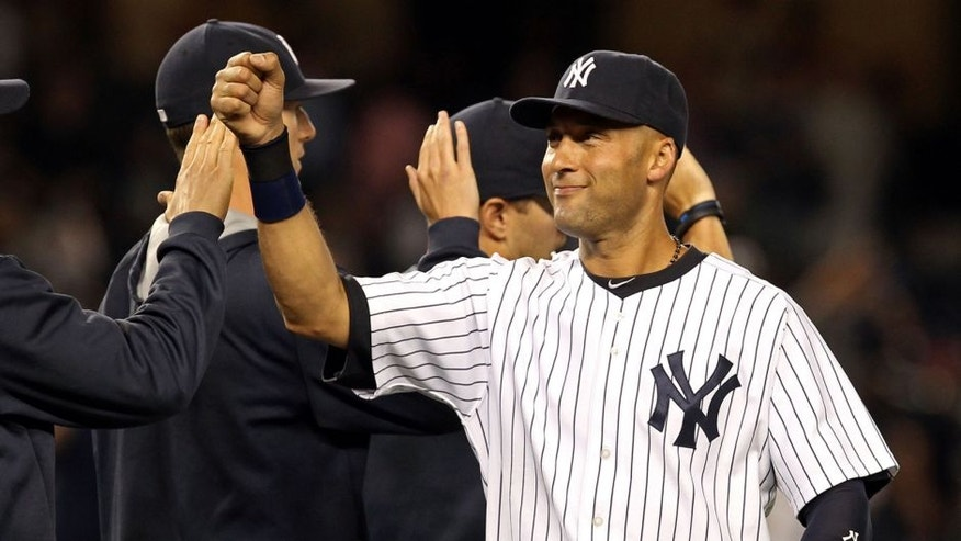 Aug 8, 2014; Bronx, NY, USA; New York Yankees shortstop Derek Jeter (2) celebrates with teammates after defeating the Cleveland Indians 10-6 at Yankee Stadium. Mandatory Credit: Adam Hunger-USA TODAY Sports