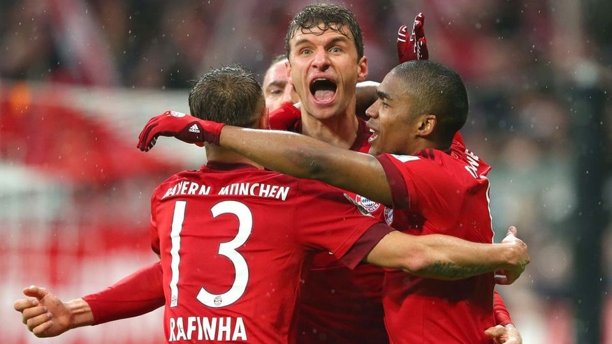 MUNICH, GERMANY - FEBRUARY 20: Thomas Mueller (C) of Muenchen celebrates scoring the 2nd team goal with his team mates Rafinha (L) and Douglas Costa during the Bundesliga match between FC Bayern Muenchen and SV Darmstadt 98 at Allianz Arena on February 20, 2016 in Munich, Germany. (Photo by A. Hassenstein/Getty Images for FC Bayern)