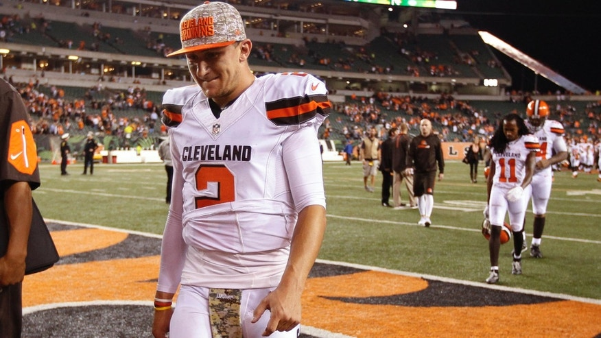 FILE- In this Nov. 5, 2015, file photo, Cleveland Browns quarterback Johnny Manziel walks off the field after the Browns lost 31-10 to the Cincinnati Bengals during an NFL football game in Cincinnati.