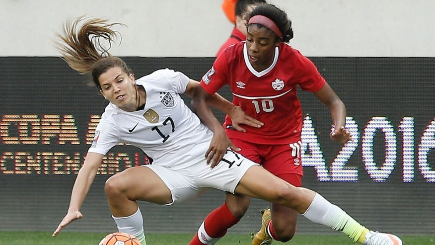 Feb 21, 2016; Houston, TX, USA; USA midfielder Tobin Heath (17) and Canada midfielder Ashley Lawrence (10) fight for possession in the first half during the 2016 CONCACAF women's Olympic soccer tournament at BBVA Compass Stadium. Mandatory Credit: Thomas B. Shea-USA TODAY Sports