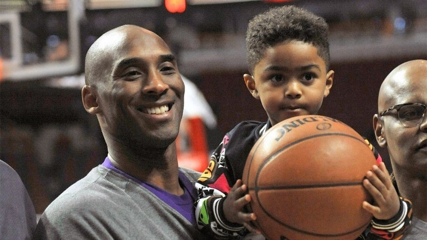Los Angeles Lakers' Kobe Bryant left, poses with Chicago Bulls' Derrick Rose's son P.J. Rose 3, before an NBA basketball game against the Chicago Bulls, Sunday, Feb. 21, 2016, in Chicago. (AP Photo/Paul Beaty)