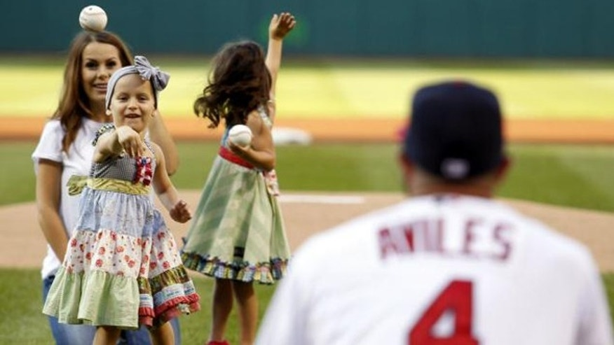 Adriana Aviles throws out the first pitch at an Indians home game to her father. (Photo: AARON JOSEFCZYK/AP)