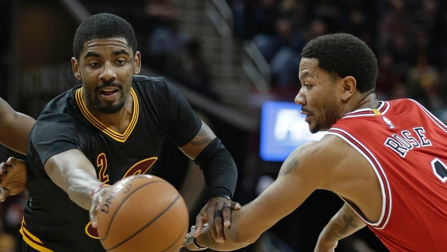 Cleveland Cavaliers' Kyrie Irving, left, passes against Chicago Bulls' Derrick Rose in the second half of an NBA basketball game Thursday, Feb. 18, 2016, in Cleveland.