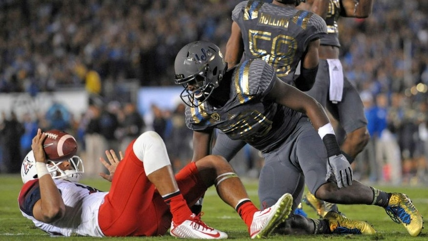 Nov 1, 2014; Pasadena, CA, USA; UCLA Bruins linebacker Myles Jack (30)reacts after sacking Arizona Wildcats quarterback Anu Solomon (left) during the first quarter at Rose Bowl. Mandatory Credit: Jake Roth-USA TODAY Sports