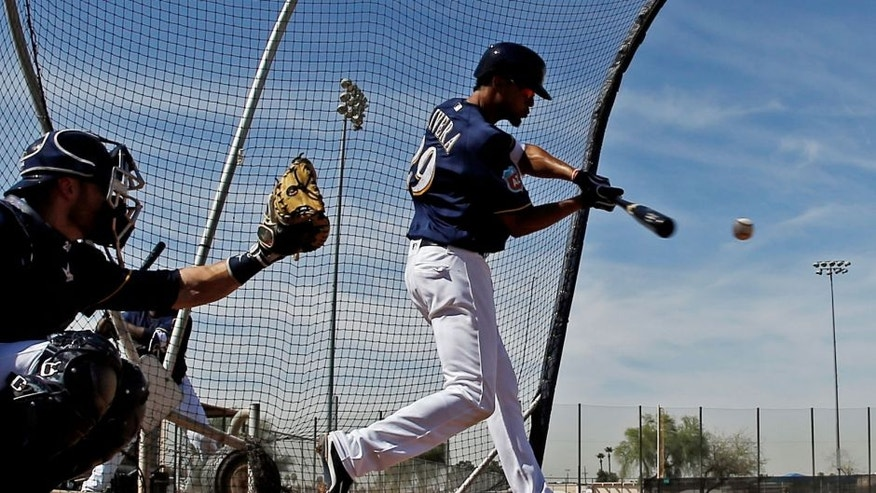 <p>Milwaukee Brewers' Yadiel Rivera hits as catcher Jonathan Lucroy watches during a spring training baseball workout Tuesday, March 1, 2016, in Phoenix.</p>