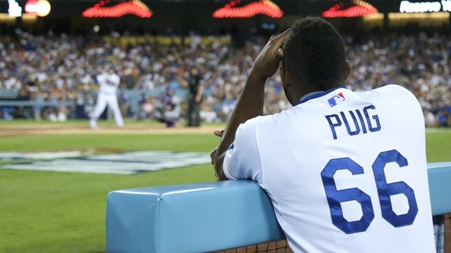 LOS ANGELES, CA - OCTOBER 10:  Yasiel Puig #66 of the Los Angeles Dodgers watches from the dugout in the third inning while taking on the New York Mets in game two of the National League Division Series at Dodger Stadium on October 10, 2015 in Los Angeles, California.  (Photo by Stephen Dunn/Getty Images)
