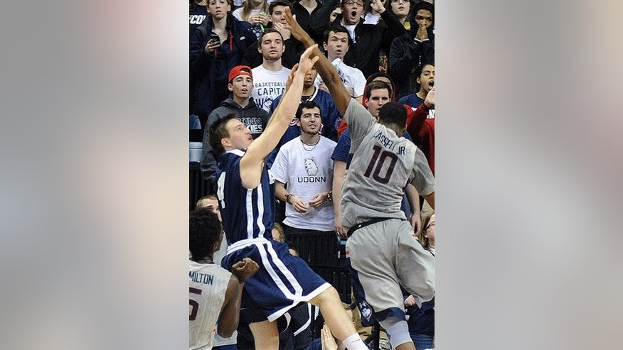 Yale's Jack Montague, left, shoots a game winning three-point shot over Connecticut's Sam Cassell Jr. (10) during the second half of Yale's 45-44 upset victory in an NCAA college basketball game in Storrs, Conn., on Dec. 5, 2014.