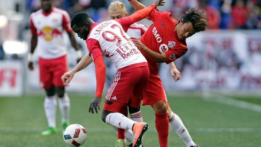 New York Red Bulls defender Kemar Lawrence (92) battles for the ball with Toronto FC midfielder Tsubasa Endoh during the first half of an MLS soccer game Sunday, March 6, 2016, in Harrison, N.J. (AP Photo/Adam Hunger)