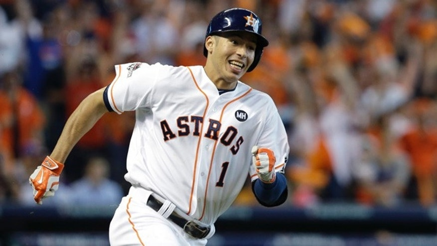 FILE - In this Oct. 12, 2015, file photo, Houston Astros' Carlos Correa races to first base after an RBI hitting a single against the Kansas City Royals during Game 4 of baseball's American League Division Series in Houston. Last year's AL Rookie of Year has a closet filled with hundreds of pairs of shoes and is constantly adding to the collection. The shoes symbolize just how far Houston's shortstop has come from a childhood in Puerto Rico where he recalls having only one pair for more than two years. (AP Photo/Pat Sullivan, File)