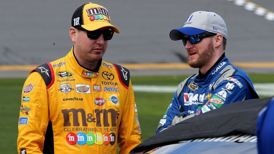 DAYTONA BEACH, FL - FEBRUARY 14: Kyle Busch, driver of the #18 M&M's 75 Toyota, talks with Dale Earnhardt Jr., driver of the #88 Nationwide Chevrolet, on the grid during qualifying for the NASCAR Sprint Cup Series Daytona 500 at Daytona International Speedway on February 14, 2016 in Daytona Beach, Florida. (Photo by Jerry Markland/Getty Images)