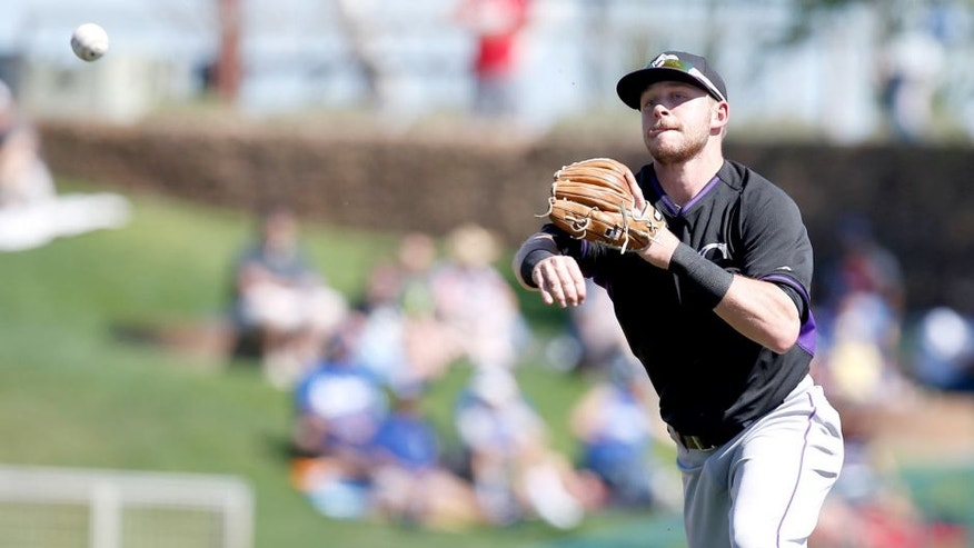 Mar 10, 2015; Phoenix, AZ, USA; Colorado Rockies shortstop Trevor Story (77) makes the off balance throw for the out against the Los Angeles Dodgers in the second inning during a spring training game at Camelback Ranch. Mandatory Credit: Rick Scuteri-USA TODAY Sports