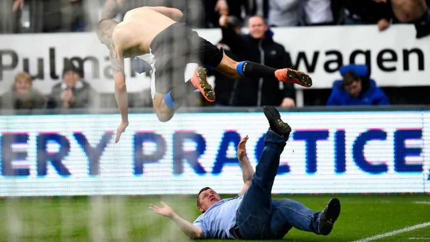 NEWCASTLE UPON TYNE, ENGLAND - MARCH 20: Aleksandar Mitrovic of Newcastle United collides with a fan as he celebrates scoring their first and equalising goal during the Barclays Premier League match between Newcastle United and Sunderland at St James' Park on March 20, 2016 in Newcastle upon Tyne, United Kingdom. (Photo by Stu Forster/Getty Images (Photo by Stu Forster/Getty Images)