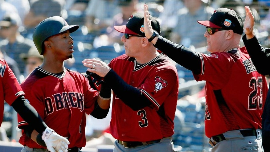 Arizona Diamondbacks' Jean Segura, left, is congratulated by manager Chip Hale (3) and pitching coach Mike Butcher (23) after scoring a run against the San Diego Padres during the second inning of a spring training baseball game Tuesday, March 8, 2016, in Peoria, Ariz. (AP Photo/Ross D. Franklin)