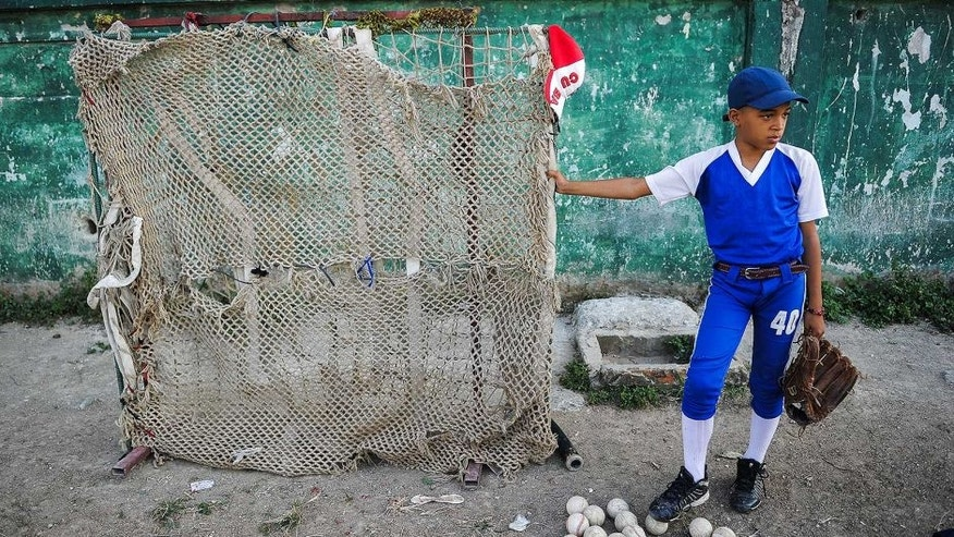 A Cuban child looks at a baseball practice in Havana, on March 16, 2016. Cubans look forward to the baseball game between the US Tampa Bay Rays team and the Cuban team, which will take place on March 22, with the presence of US President Barack Obama. AFP PHOTO/ YAMIL LAGE / AFP / YAMIL LAGE (Photo credit should read YAMIL LAGE/AFP/Getty Images)
