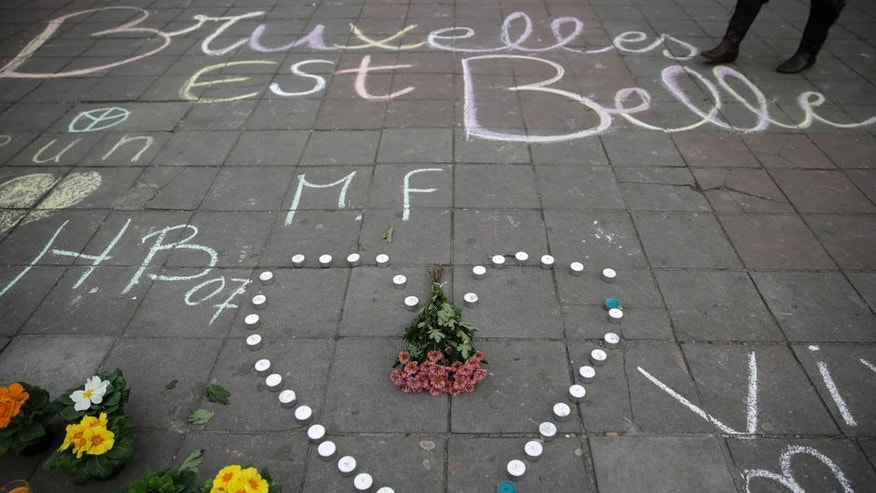 "A message written on the ground reads ""Brussels is beautiful"" next to flowers and candles following attacks in Brussels on March 22, 2016. Airlines cancelled hundreds of flights and European railways froze links with Brussels after a series of bomb blasts killed around 35 people in the city's airport and a metro train, sparking a broad security response. AFP PHOTO / KENZO TRIBOUILLARD / AFP / KENZO TRIBOUILLARD (Photo credit should read KENZO TRIBOUILLARD/AFP/Getty Images)"