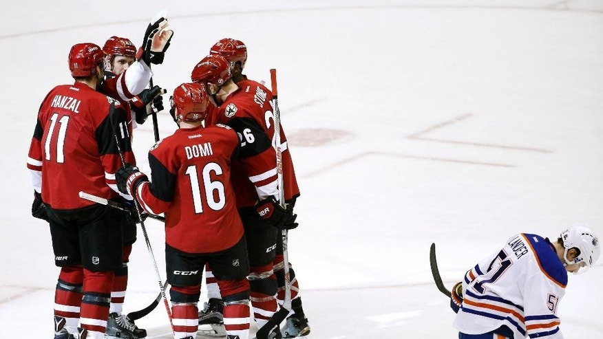 Arizona Coyotes' Martin Hanzal (11), of the Czech Republic, celebrates his goal with Max Domi (16), Michael Stone (26), Anthony Duclair, and Oliver Ekman-Larsson, second from left, of Sweden, as Edmonton Oilers' Anton Lander (51), of Sweden, skates past during the second period of an NHL hockey game, Tuesday, March 22, 2016, in Glendale, Ariz. (AP Photo/Ross D. Franklin)