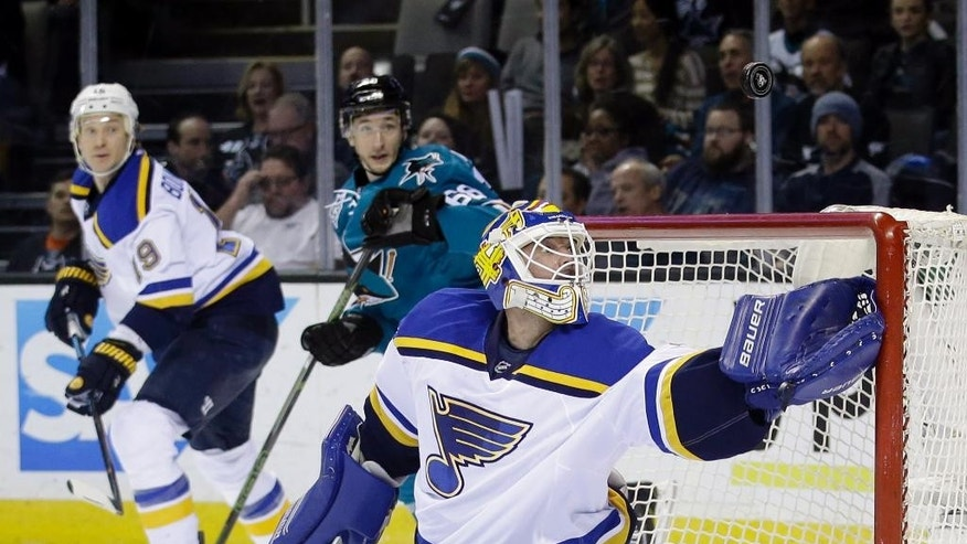 St. Louis Blues goalie Brian Elliott, right, deflects a shot against the San Jose Sharks during the first period of an NHL hockey game Tuesday, March 22, 2016, in San Jose, Calif. (AP Photo/Marcio Jose Sanchez)